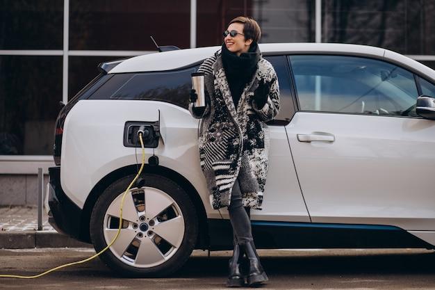 通りで電気自動車を充電する女性 無料写真