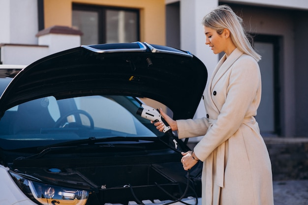 Woman charging electro car by her house and holding charger Free Photo