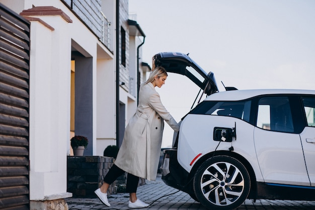 Woman charging electro car by her house Free Photo