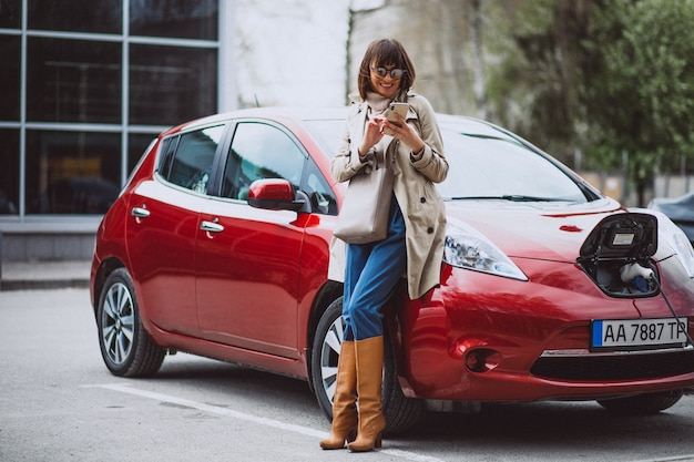 Woman charging electro car at the electric gas station Free Photo