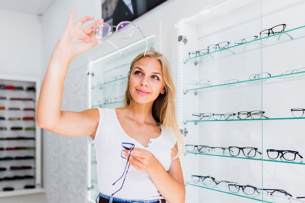 Woman checking eyeglasses frame in store Free Photo