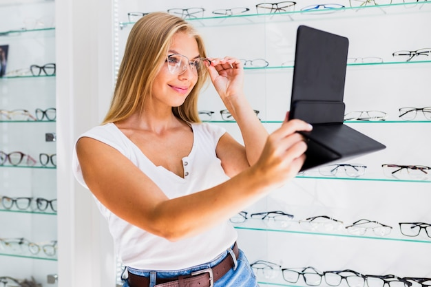 Woman checking glasses frame in mirror Free Photo