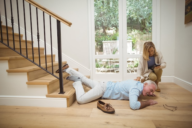 Woman checking her mobile phone while senior man fallen downstairs Premium Photo