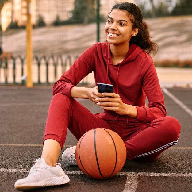 Женщина проверяет свой телефон рядом с баскетбольным мячом Бесплатные Фотографии