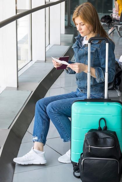 Женщина проверяет свой билет на самолет Premium Фотографии