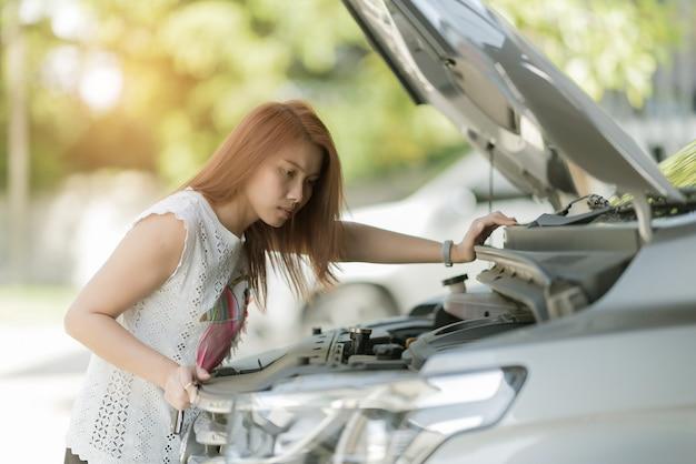 Женщина проверяет уровень масла в машине, меняет масло в машине Premium Фотографии