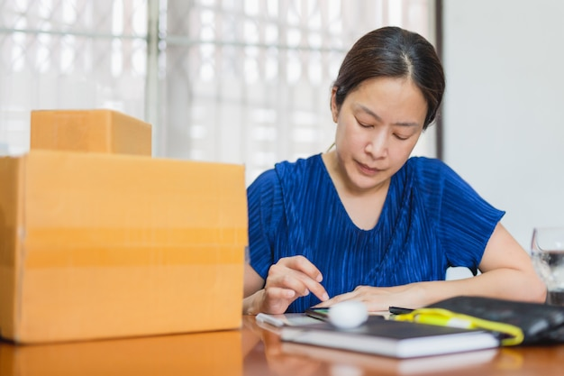 Woman checking order in cell phone for delivery package to customer from home office. Premium Photo