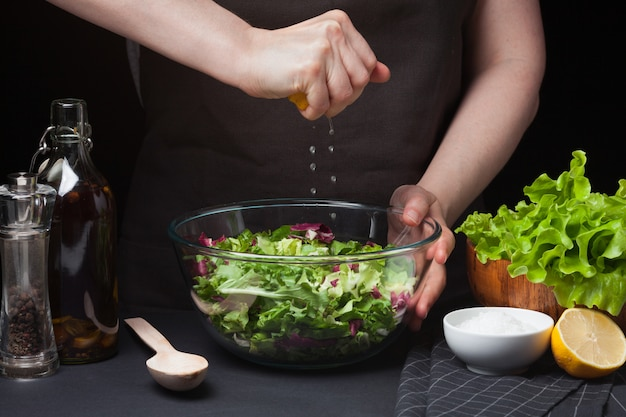 Woman chef in the kitchen preparing salad. Premium Photo