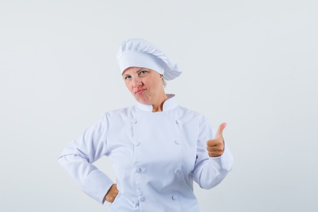 Woman chef showing thumb up in white uniform and looking pleased Free Photo