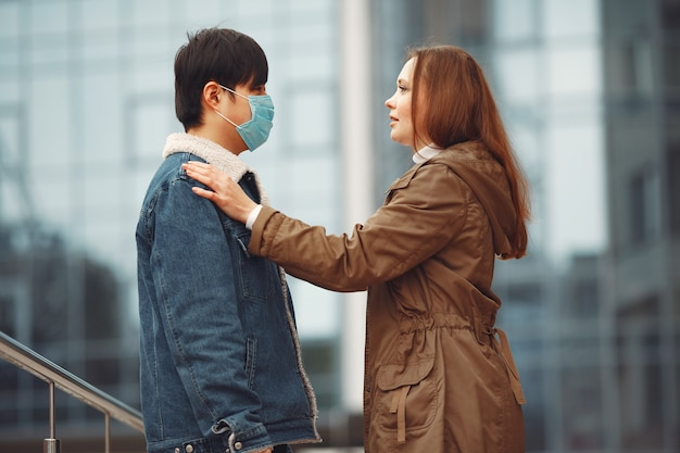 A woman and chinese man are wearing protective masks Free Photo