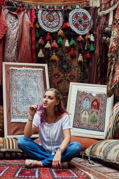 Woman chooses carpet at the market. Premium Photo
