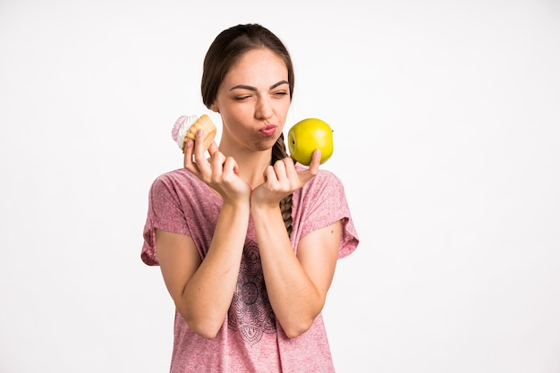 Woman choosing between apple and cupcake Premium Photo