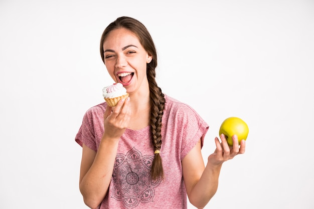 Woman choosing cupcake over apple Free Photo