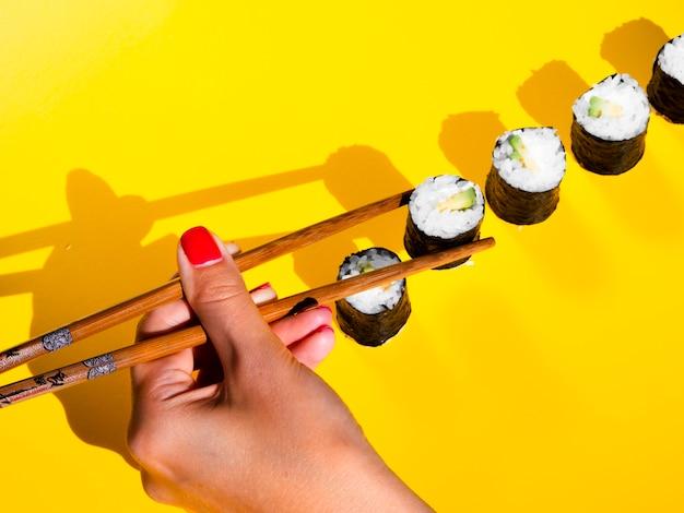 Woman choosing a nigiri roll from a yellow table Free Photo