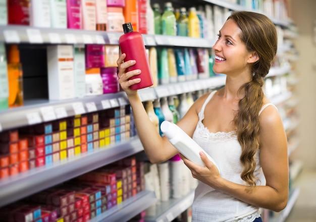 Woman choosing shampoo at store  Premium Photo