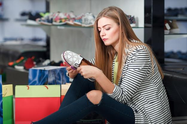 Женщина, выбирающая обувь Premium Фотографии