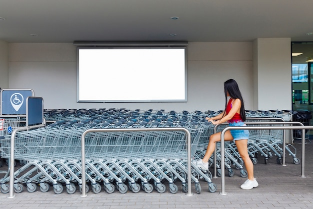 Woman choosing shopping trolley in parking lot for carts Free Photo
