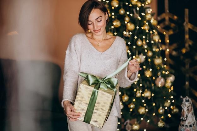 Woman on christmas holding a christmas present by the christmas tree Free Photo