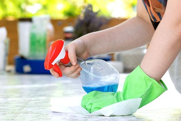 Женщина чистит и протирает стол Premium Фотографии