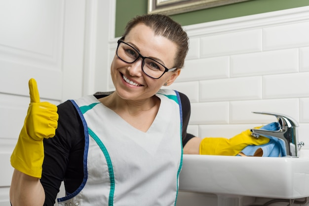 Woman in cleaning clothes giving thumbs up Premium Photo