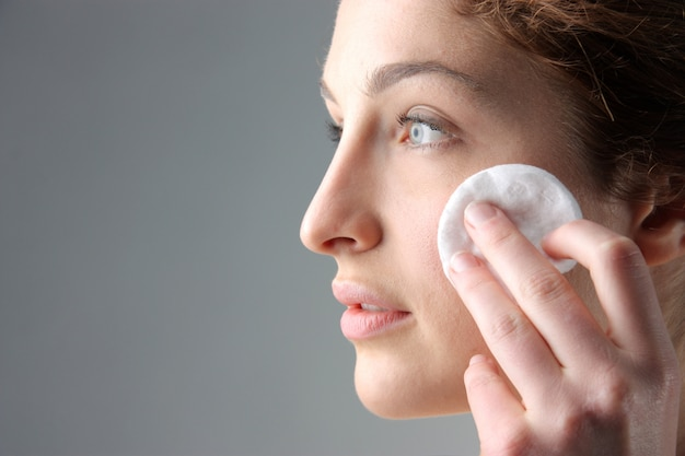 Woman cleaning face with cotton disk Premium Photo