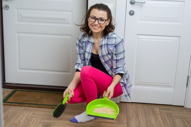Woman cleaning floor with broom and dust pan Premium Photo