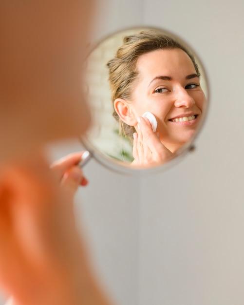 Donna che pulisce il viso allo specchio Foto Gratuite