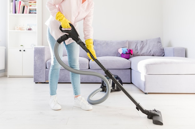 Woman cleaning her home with vacuum cleaner Free Photo