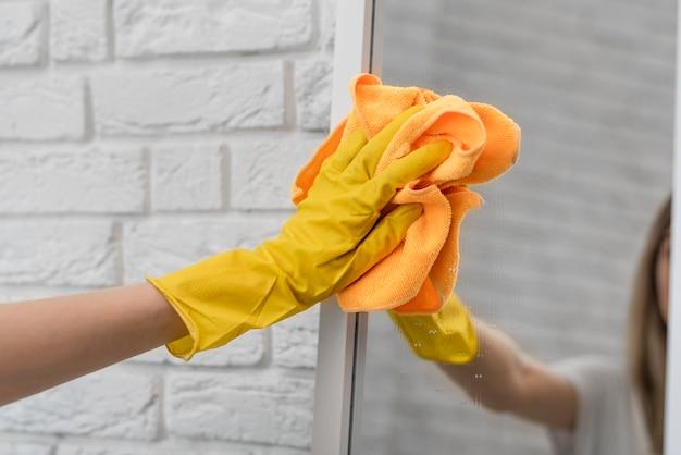 Женщина чистит зеркало с тканью Premium Фотографии