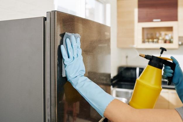 Женщина, чистящая холодильник Premium Фотографии