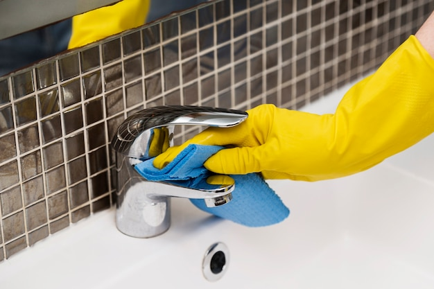 Женщина чистит раковину в ванной Premium Фотографии