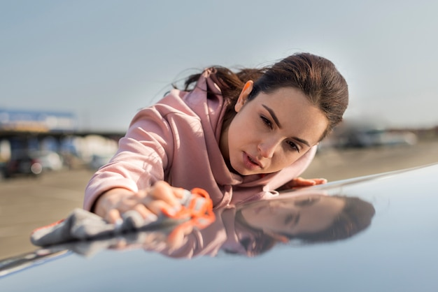 車のフロントビューのボンネットを掃除する女性 無料写真