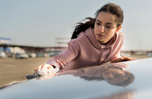 Женщина чистит капот машины Бесплатные Фотографии