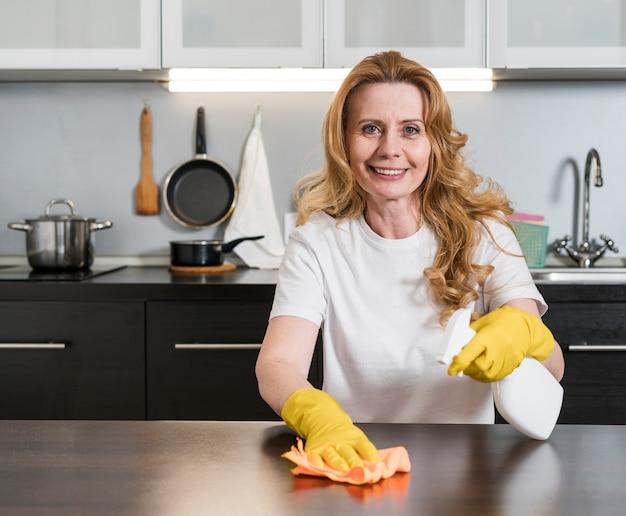 台所のテーブルを掃除する女性 無料写真