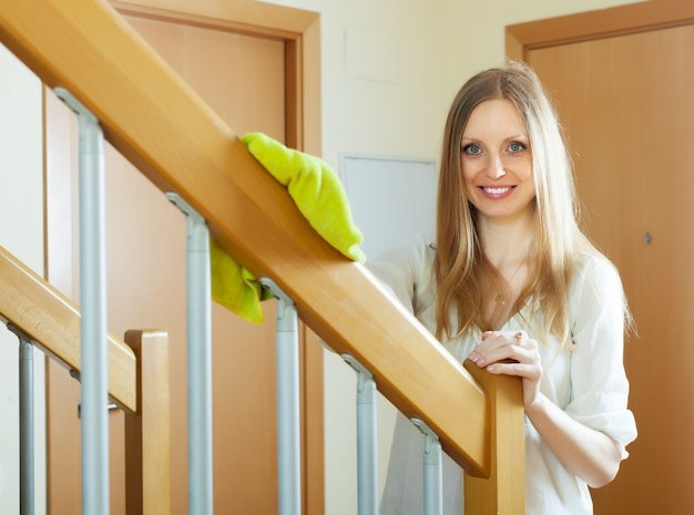 Woman cleaning wooden stair railings at home Free Photo