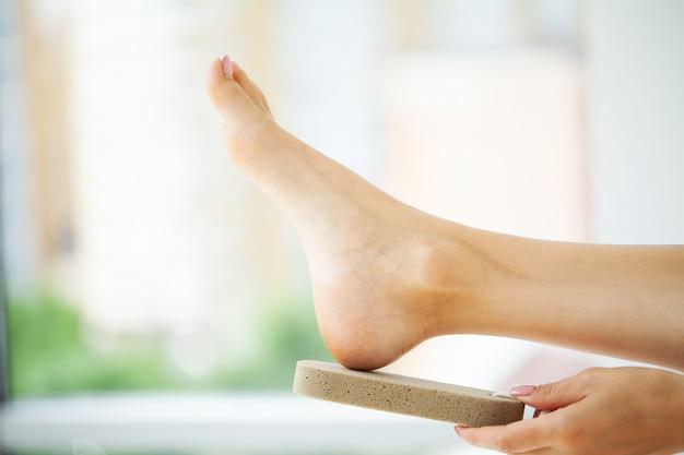 Женщина чистит пятку стопы с помощью пемзы Premium Фотографии