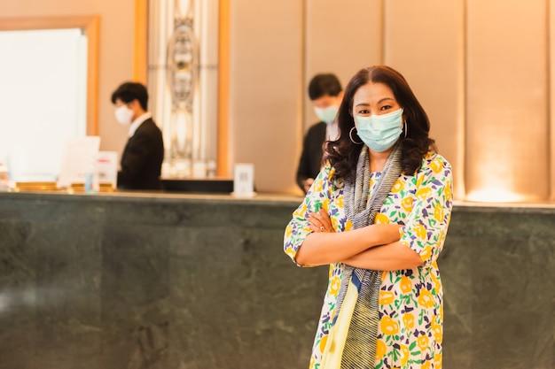ホテルのフロントの前に立っている医療マスクを着ている女性クライアント。 Premium写真