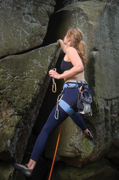 Woman climber climbing a big rock and holding carbines. Premium Photo
