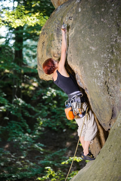 Woman climber climbing rocky wall and clipping carbine Premium Photo