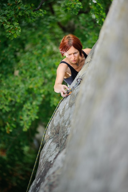 Woman climbing steep cliff wall in summer time belaying herself Premium Photo