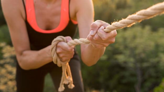 Женщина, восхождение с помощью веревки Premium Фотографии