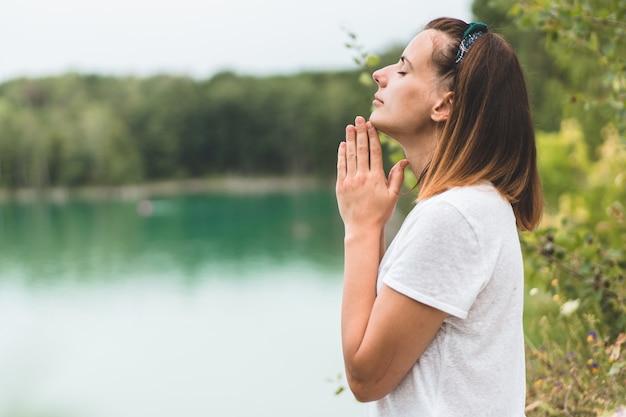 女性は屋外で祈りながら目を閉じた。信仰、霊性、宗教の祈りの概念に折り畳まれた手 Premium写真