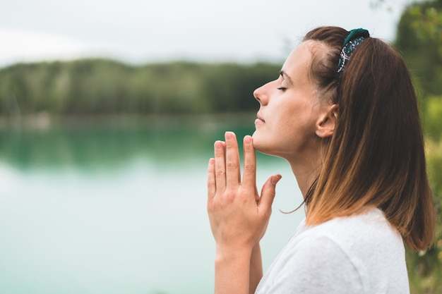 Woman closed her eyes, praying in outdoors. hands folded in prayer concept for faith, spirituality and religion Premium Photo