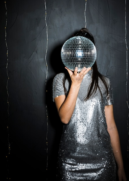 Woman closing face by disco ball Free Photo