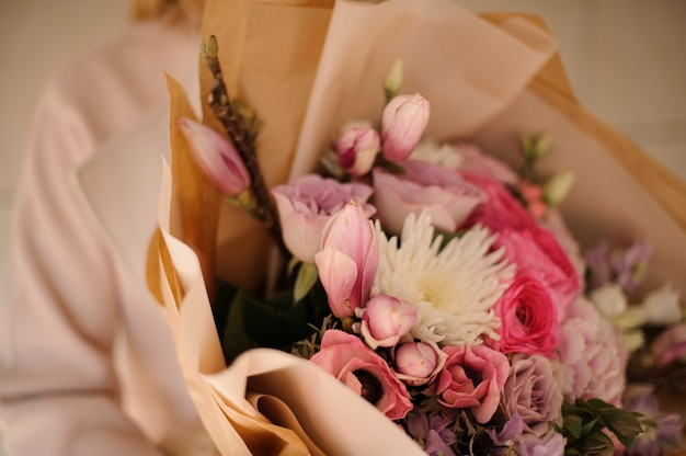 Woman in the coat holding a bouquet of tender color pink flowers Premium Photo