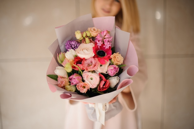 Woman in the coat holding a bouquet of tender color pink multicolored flowers Premium Photo