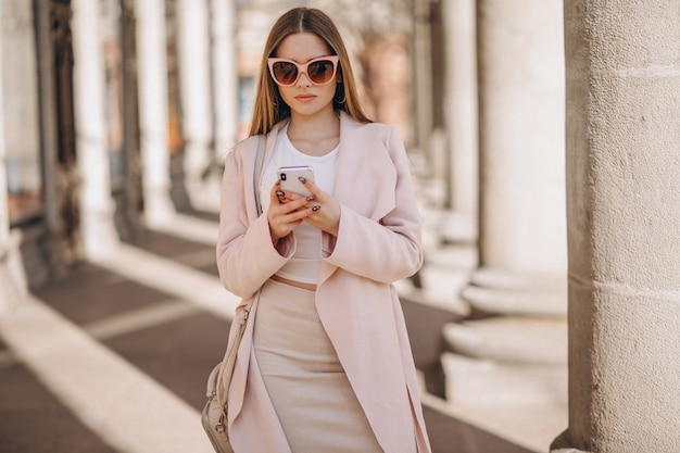 Woman in coat walking in the street and talking on the phone Free Photo