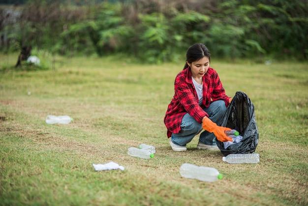 Donna che raccoglie immondizia in una borsa nera. Foto Gratuite