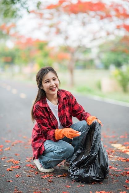 Женщина собирает мусор в черной сумке. Бесплатные Фотографии
