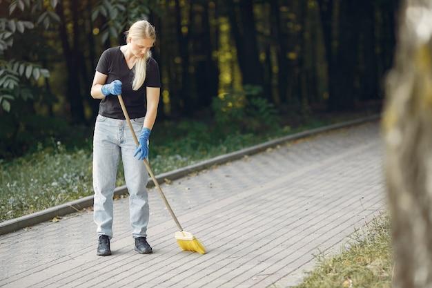 女性が葉を集めて公園を掃除する 無料写真